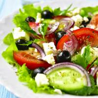 Traditional greek salad on a white plate over rustic wooden background.