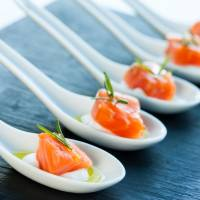 Numerous porcelain spoons with smoked salmon morsels.